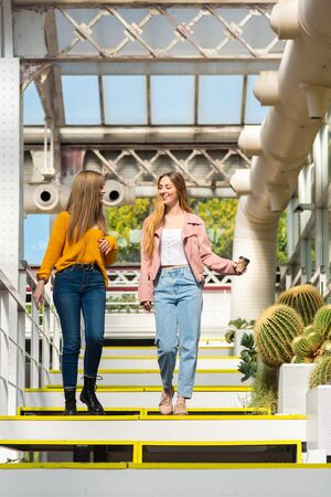 Two young blond-haired Caucasian women walk down stairs inside an urban greenhouse with the white frame surrounded by plants and cacti 版權商用圖片