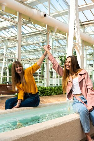 Two attractive young Caucasian girls with blonde hair shake hands with their arms in the air smiling at a fountain inside a brightly lit room with the white structure