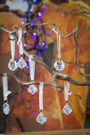 plastic christmas tree: Faceted crystal Christmas decorations shaped as droplets and stars or snowflakes hanging on the dried branches of a modern Christmas tree to celebrate the festive season, close up background view