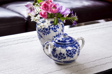 Centrepiece: Fresh summer flowers in an oriental style blue and white china ginger jar on a table with a matching sugar basin as a centrepiece to a tea table