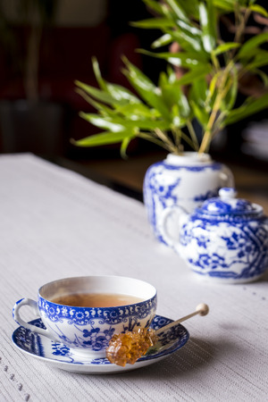 sweetening: Cup of freshly brewed black tea served in a dainty blue and white porcelain cup and saucer with a sugar crystal stick for sweetening