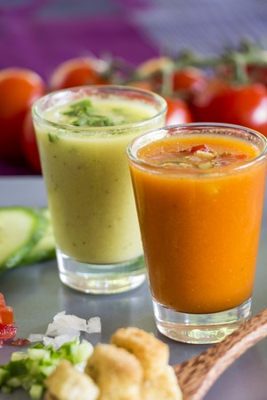 Two glasses of chilled gazpacho soup, one green and one orange, with fresh ripe cherry tomatoes and sliced cucumber ingredients photo