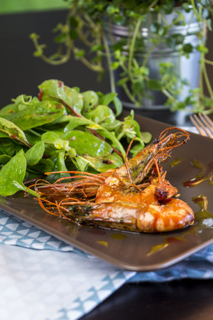 baby spinach: Delicious gourmet seafood appetizer of three whole grilled seasoned pink prawns with baby spinach and herbs on a rectangular platter