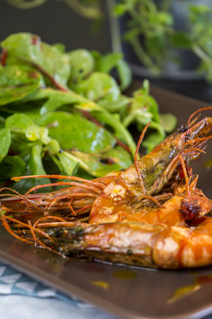 'baby spinach': Delicious gourmet seafood appetizer of three whole grilled seasoned pink prawns with baby spinach and herbs on a rectangular platter