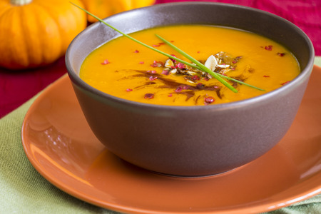 Bowl of delicious pumpkin soup garnished with fresh chives with a colorful display of ornamental gourds in the background photo
