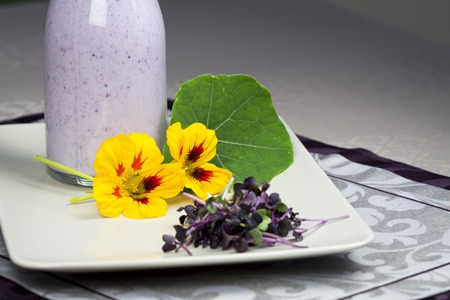 edible leaves: Glass bottle of fresh homemade yoghurt with garden herbs and colorful edible nasturtium flowers and leaves on a plate served outdoors in the garden