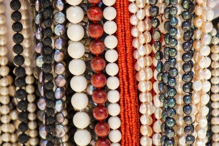 calcium carbonate: Strings of matched cultured pearl necklaces with black and white lustrous nacre beads hanging on a display in a shop in Mauritius Stock Photo