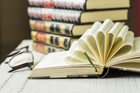 tooled leather: Libro aperto rigida con pagine piegate decorative disposte a ventaglio radiante sdraiata su un tavolo davanti a una pila di rilegati in pelle dorato lavorato libri