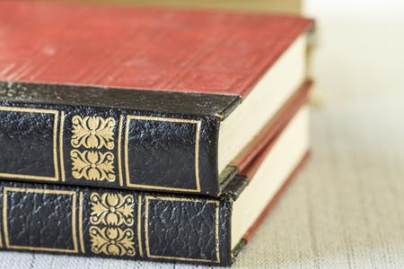 tooled leather: Texture di due cuoio dorato legato lavorato libri d'epoca con motivi decorativi sulle spine di fronte al saldo del set impilati su un tavolo, da vicino i dettagli
