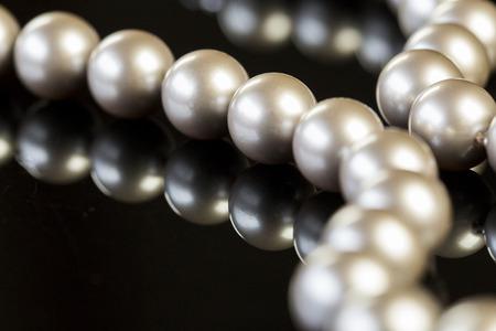 emphasizing: Close up Elegant Pearl Necklace on Glossy Table, Emphasizing Reflection Image.