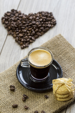 addictive drinking: Strong mug of freshly brewed espresso coffee with coffee beans with a dainty pile of crunchy cookies tied together on a hessian cloth Stock Photo