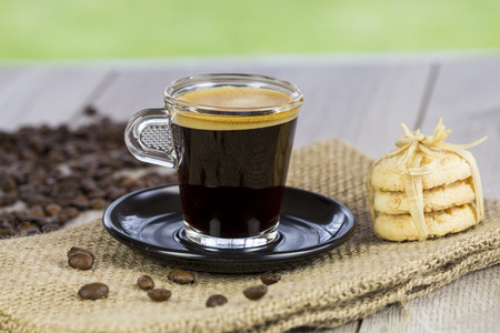 energizing: Strong mug of freshly brewed espresso coffee with coffee beans with a dainty pile of crunchy cookies tied together on a hessian cloth Stock Photo