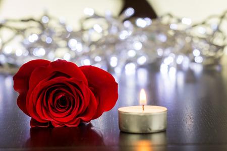 魅力的な新鮮な赤いバラの花と木のテーブルに小さな点灯ろうそくを閉じる