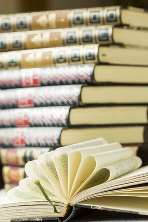 radiating: Libro aperto rigida con pagine piegate decorative disposte a ventaglio radiante sdraiata su un tavolo davanti a una pila di rilegati in pelle dorato lavorato libri