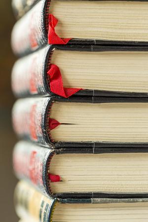 columna vertebral: Textura de dos libros de cuero dorado con destino labrado de la vendimia con los patrones decorativos en las espinas frente al equilibrio del conjunto apilados sobre una mesa, de cerca los detalles