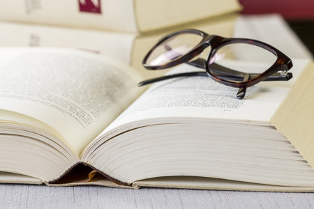 volumes: Pair of black framed reading glasses on an open book lying on a table with tablecloth in front of a stack of leather bound retro hardcover volumes Stock Photo