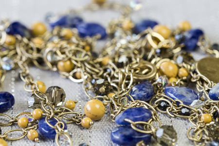 sodalite: Close Up of Gold Jewelry Chain Necklace with Yellow Beads and Blue Stone Accents