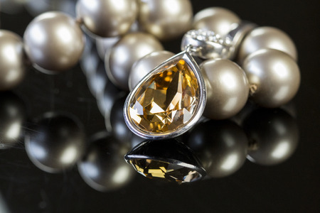pearl background: Close up Elegant Pearl Necklace on Glossy Table, Emphasizing Reflection Image.