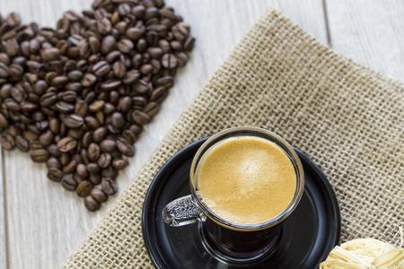 Hessian 布に一緒に結ばれるカリカリ クッキーの可憐な山とコーヒー豆で入れたてのエスプレッソ コーヒーの強いマグカップ