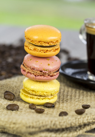 tilted: Batch of freshly baked colorful macarons made from egg white, coconut, almond and sugar and filled with ganache or butter cream, tilted angle view