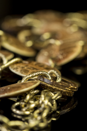 interlinked: Close up Elegant Golden Chain Fashion Accessories on Top of Glossy Table.