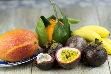 Selection of healthy ripe exotic tropical fruit with a mango, bananas, passion fruit or granadilla, and farm orange on rustic wooden boards photo