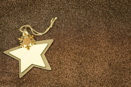 seasonal greeting: Rustic textured Christmas star background in shades of brown decorated with a golden snowflake with plenty of copyspace for your seasonal greeting Stock Photo