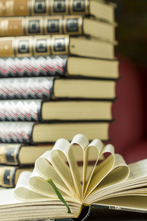 Open hardcover book with decorative folded pages arranged in a radiating fan lying on a table in front of a stack of leather bound gilt tooled books Stock Photo