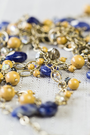 accents: Close Up of Gold Jewelry Chain Necklace with Yellow Beads and Blue Stone Accents