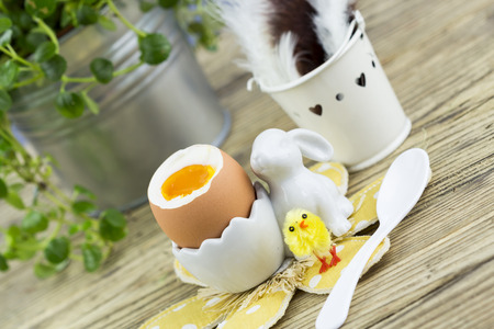 egg cup: Hard boiled egg for Easter morning breakfast served in a cute egg cup with feet on a floral mat with an Easter chick