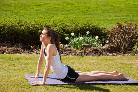 cardiovascular exercising: Attractive Young Healthy Woman Doing Stretching Exercise in Yoga at the Poolside on One Sunny Day.