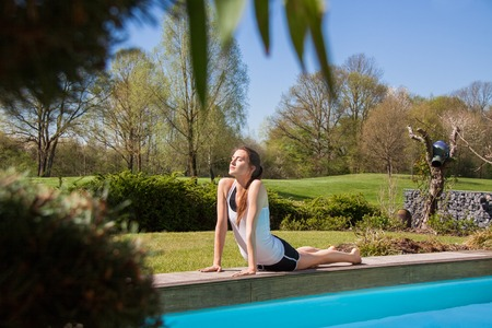 centering: Attractive Young Healthy Woman Doing Stretching Exercise in Yoga at the Poolside on One Sunny Day.