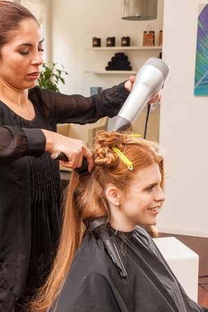 hair stylist: Profile of Smiling Young Woman with Long Red Hair Having Hair Cut and Styled by Stylist in Salon