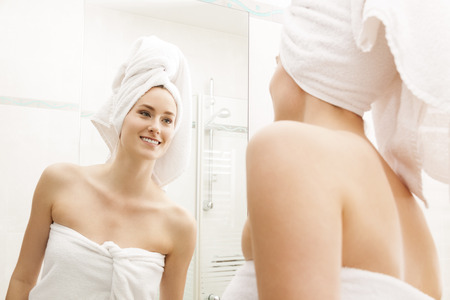 bathroom woman: Young Woman Fresh From Shower, Wrapped with White Towels, Looking Herself at the Mirror In the Bathroom While Touching her Face.