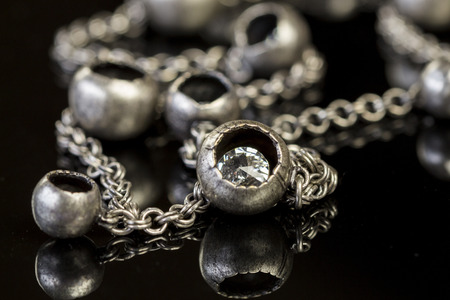 costume jewellery: Assorted silver costume jewellery with a jumbled pile of chains with different shaped links, a clear crystal bead and a necklace of round silver beads with focus to the chains