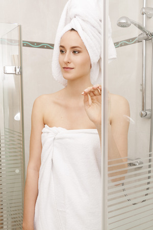 shower cubicle: Fresh Young Woman Wrapped with Towels After Bath, Smiling at the Camera While Inside the Shower Cubicle