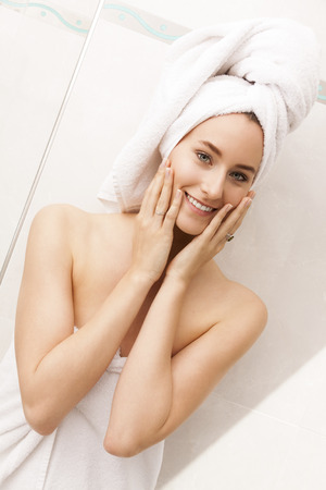 demure: Close up Pretty Young Woman Wrapped in Towels After Bath, Caressing her Face While Looking Down Seriously Stock Photo