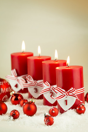 themed: Festive red themed Christmas background with an oblique row of burning candles with number tags nestling in fresh winter snow with a selection of red baubles