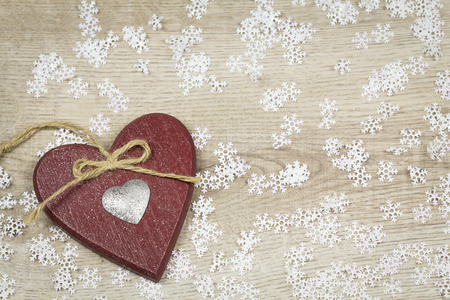seasonal greeting: Handmade decorative brown textile Christmas heart background on a wood texture with scattered white winter snowflakes for a rustic seasonal greeting Stock Photo