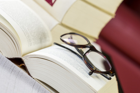 tomes: Pair of black framed reading glasses on an open book lying on a table with tablecloth in front of a stack of leather bound retro hardcover volumes Stock Photo