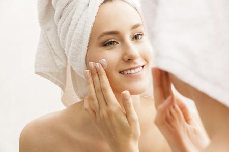 Aantrekkelijke jonge vrouw gehuld met badhanddoeken, toepassing van crème op haar gezicht na een douche in de badkamer. Stockfoto