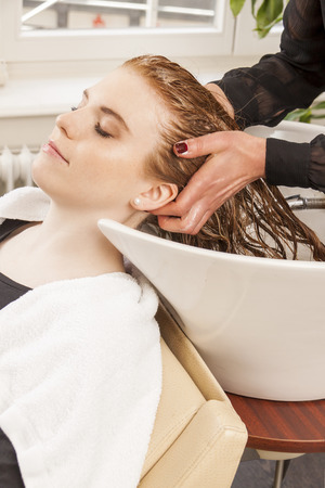 shampooing: Hairdresser washing a clients hair in a modern basin in her hairdressing salon as she prepares to style and cut her hair Stock Photo