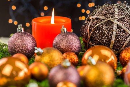 religious holiday: Burning red advent candle with brown and coppery themed Christmas baubles and a sparkling bokeh of party lights in the background for a festive seasonal celebration Stock Photo