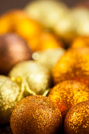 christian festival: Golden Christmas bauble background with selective focus to a single glitter ball in the foreground with a blurred pile behind giving a warm ambiance and copyspace for your seasonal greeting