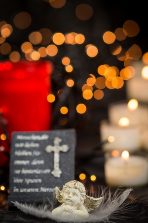 memorial: Religious Themed Still Life of Prayer Statue on Altar Illuminated with Lit Candles with Central Copy Space