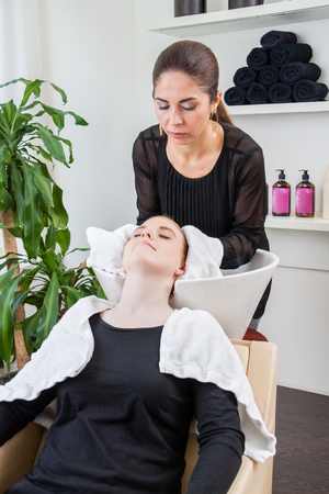 hairstyling: hairstyling professional washing woman hair at the salon