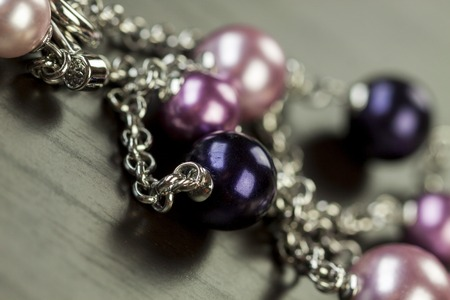 silver jewellery: Assorted silver costume jewellery with a jumbled pile of chains with different shaped links, a clear crystal bead and a necklace of round silver beads with focus to the chains