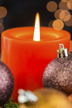 coppery: Burning red advent candle with brown and coppery themed Christmas baubles and a sparkling bokeh of party lights in the background for a festive seasonal celebration Archivio Fotografico