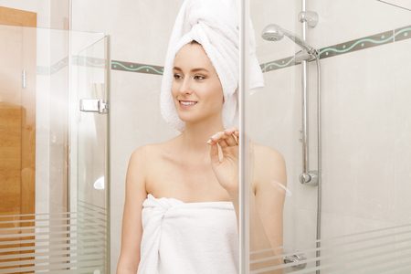 woman in towel: Fresh Young Woman Wrapped with Towels After Bath, Smiling at the Camera While Inside the Shower Cubicle