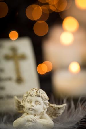 cruz religiosa: Imagen religiosa de Navidad temáticas con la oración y la estatua del ángel delante de las velas del Lit en fondo oscuro con luces parpadeantes